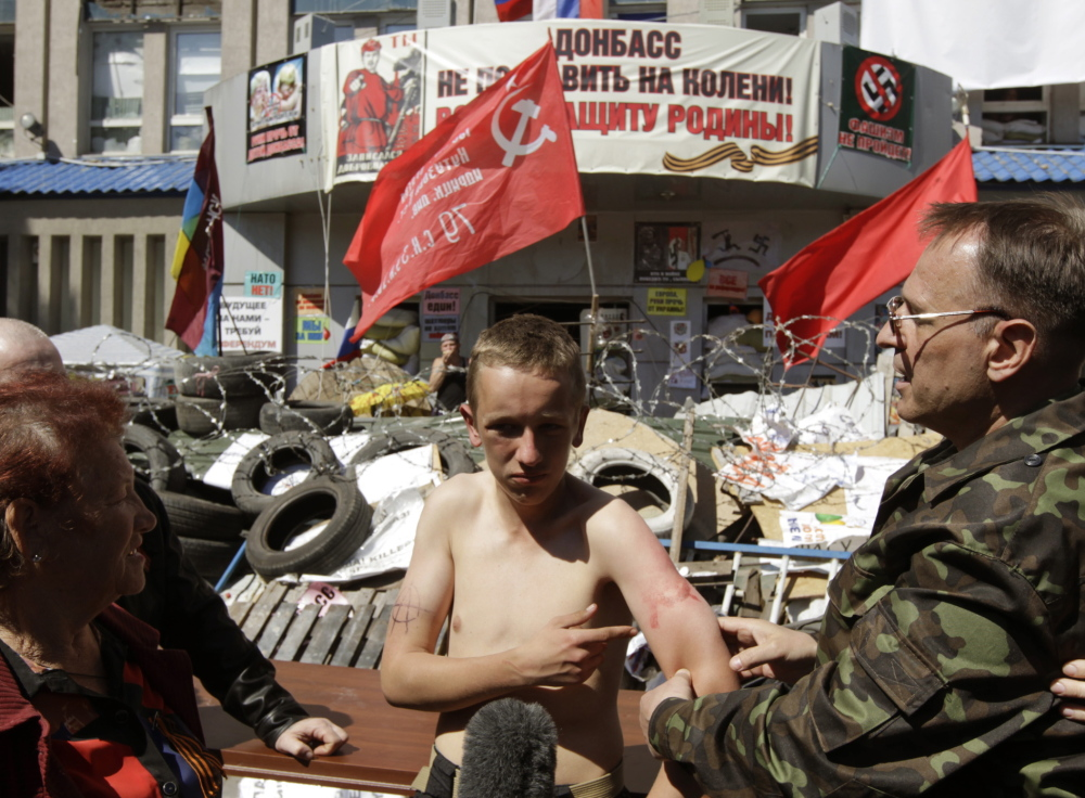 Pro-Russian separatists surround a 16-year-old boy they say is a member of a pro-Ukrainian group, near the seized office of the state security service in Luhansk on Friday.