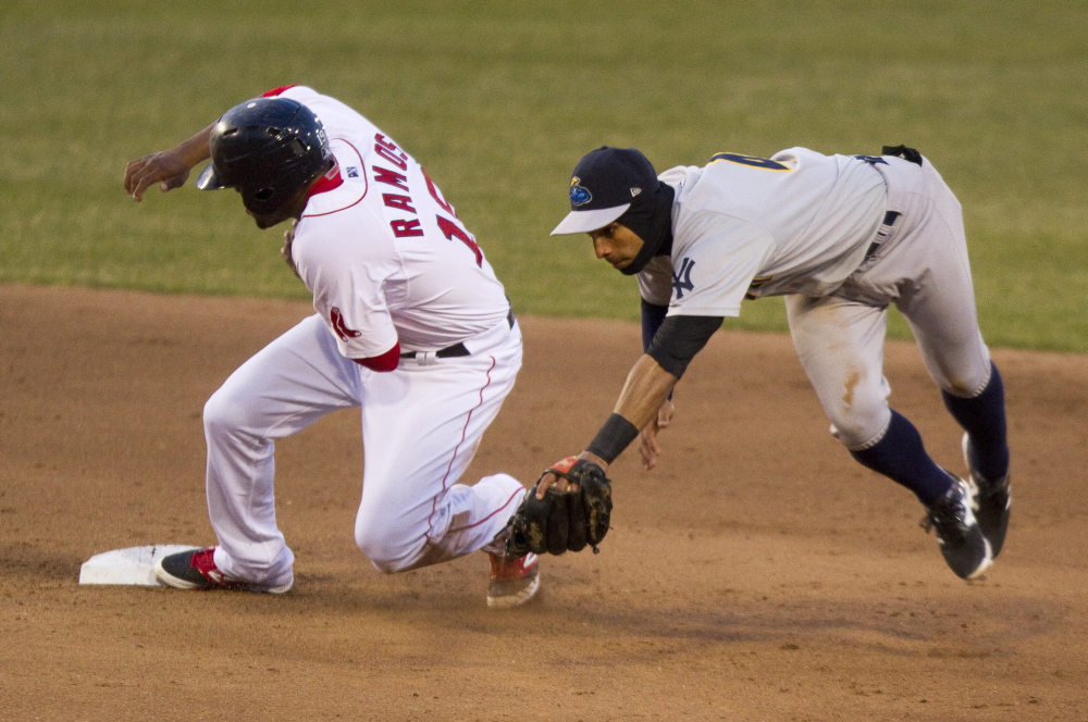Henry Ramos of the Portland Sea Dogs pulls safely into second base Friday night as shortstop Ali Castillo of the Trenton Thunder tries to handle the throw.