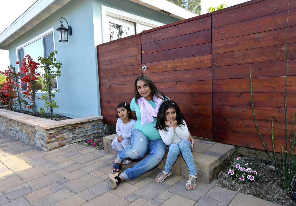 """Aniqa Jaswal poses with her daughters, Arissa, right, and Jayda on the front stoop of their home in La Jolla, Calif. After years of renting, Jaswal and her husband needed a """"jumbo"""" mortgage to buy the four-bedroom house. Jumbos are a necessity for nearly everyone in communities such as La Jolla."""
