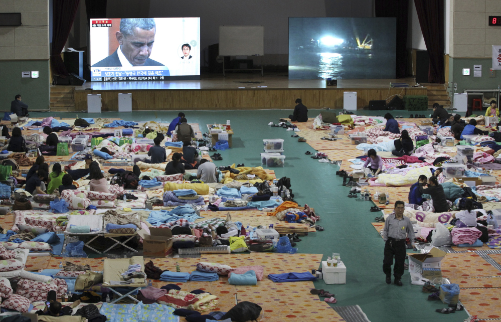 A TV screen shows President Barack Obama paying a silent tribute for the victims of South Korea's sunken ferry Sewol during a summit meeting with South Korean President Park Geun-hye as relatives of victims looks on at a gymnasium in Jindo Friday.