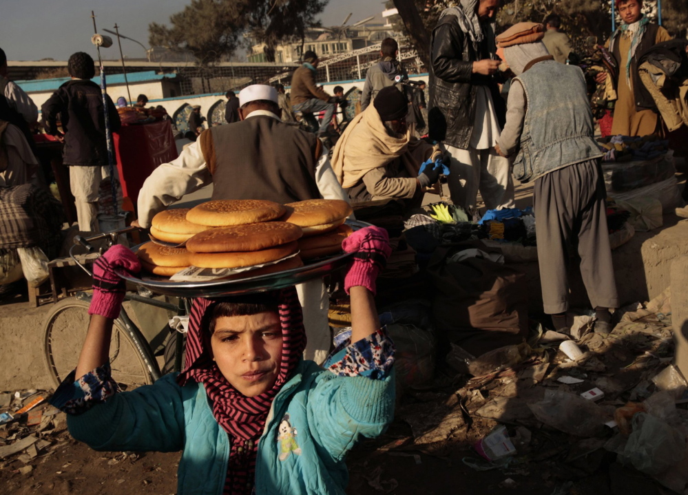 A young girl works selling bread in downtown Kabul. Child labor is pervasive in Afghanistan because of the need to have family members earning income.