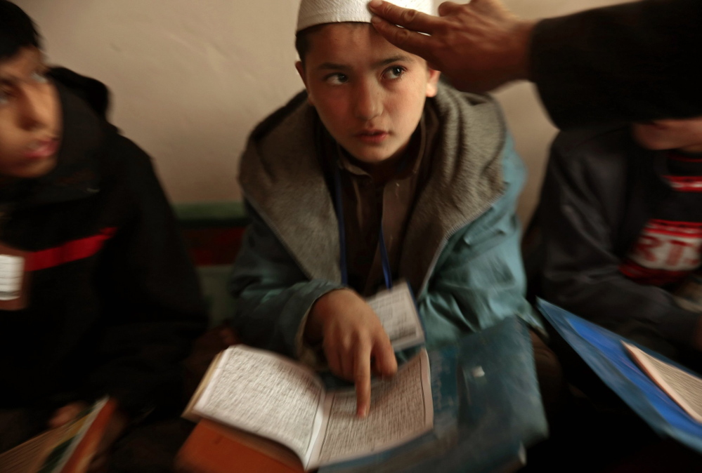 Sami Rahimi attends Islamic religious school classes for an hour each day. Rahimi, 13, lives and works in a bread bakery in Kabul, Afghanistan. He earns about $3 per day to help support his family, which lives in a northern province.