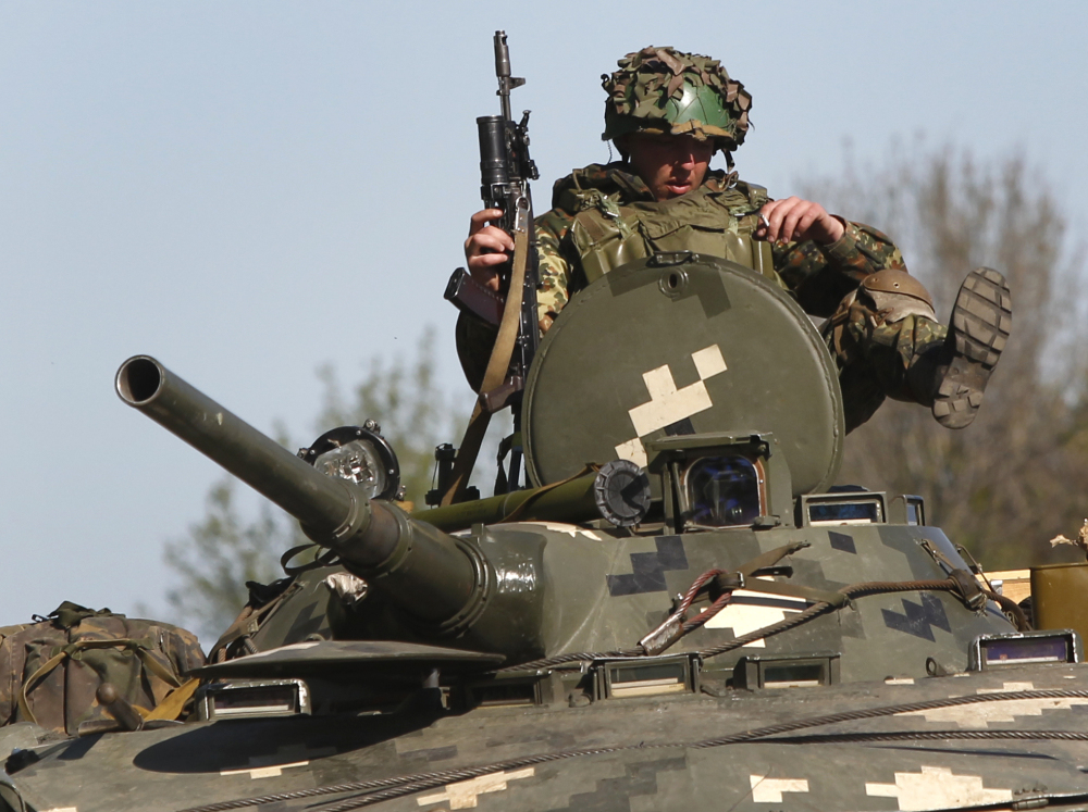 Ukrainian troops sit atop their armored personnel carrier as they guard a checkpoint near the village of Dolina, 18 miles from Slovyansk, in eastern Ukraine on Saturday.