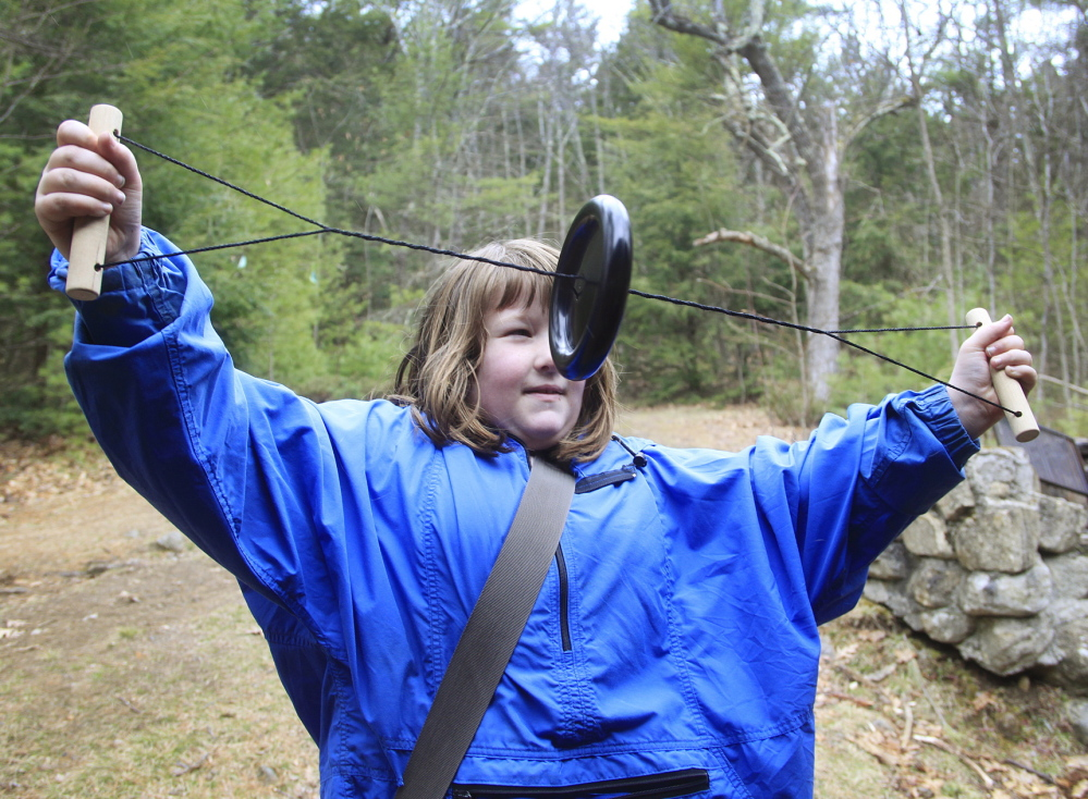 Ariella Searfoss, 7, of Pownal pulls the strings on a Loon Tune birdcalling device to listen to the call of a loon while waiting for the birds of prey presentation.