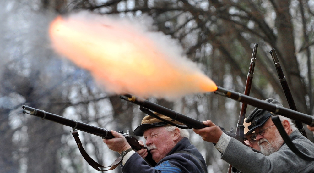 Civil War re-enactors of the Confederate Army's 15th Alabama, Company G, perform a firing demonstration Saturday during a re-enactment at Abbott Park in Farmington.