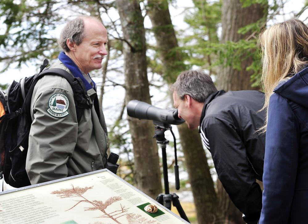 Park manager Andy Hutchinson lets Tom and Kristen Sandock – two visitors from Boxborough, Mass. – look through his 60x power scope at the Googins Island osprey nest in Wolfe's Neck Woods State Park in Freeport. As they watch, he tells them about the osprey nesting program.