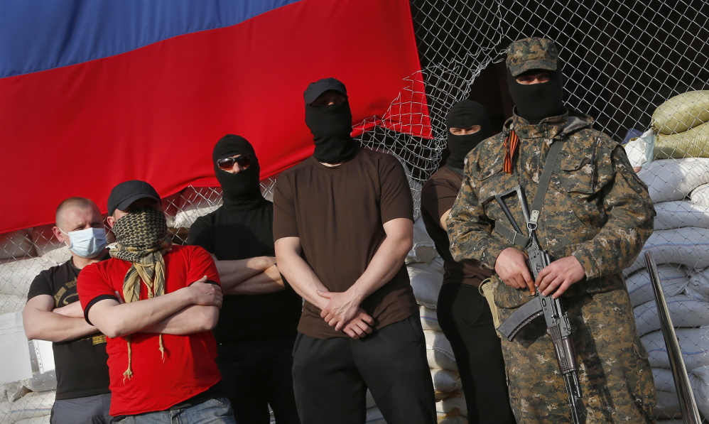 Masked pro-Russian armed men stand at city hall during negotiations about the release of foreign military observers being held by insurgents in Slovyansk, eastern Ukraine, on Sunday.