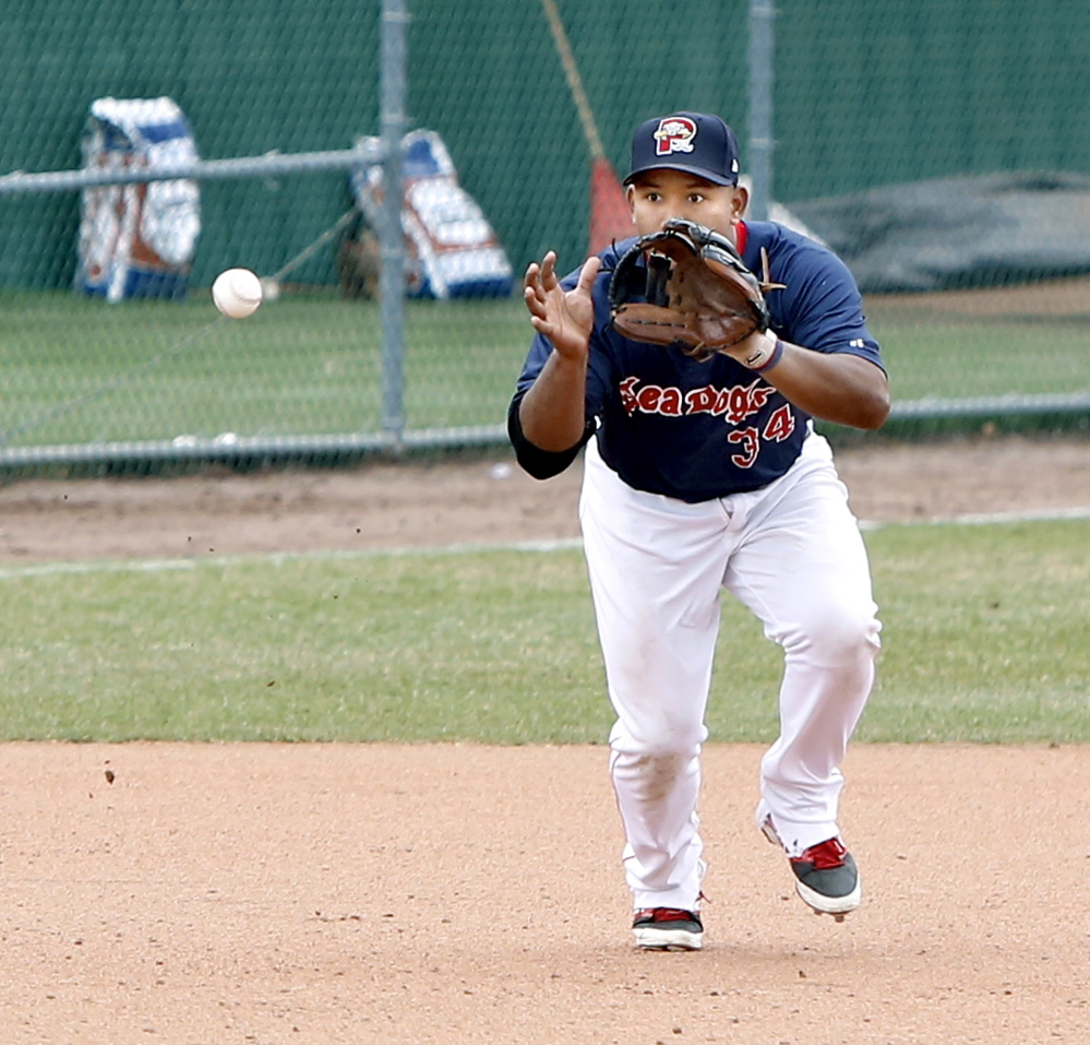 Sea Dogs third baseman Heiker Meneses watches a ground ball into his glove against the Trenton Thunder on Sunday.