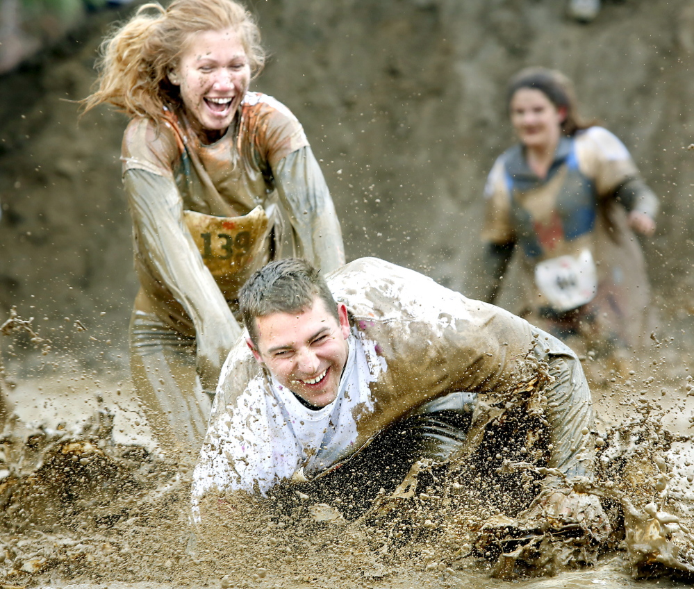 Melissa Laughlin makes sure Blake Laughlin gets the full experience of a mud pit Sunday during the Into the Mud Challenge. The 2.5-mile course at Gorham Middle School was dotted with mud and obstacles to challenge the nearly 1,000 racers.