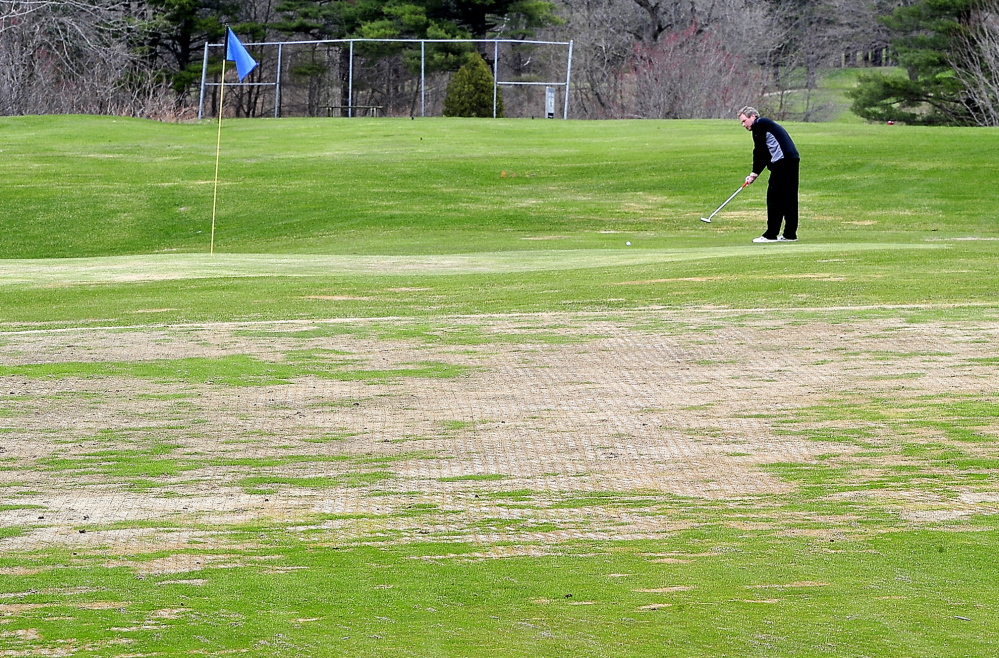 "Andy McInnis of Portland, a member of Riverside Golf Course for the past 20 years, putts Monday on the temporary green at the 6th hole. It is one of many greens that have been adversely affected by winter ice at Riverside and other local courses. ""This is the worst I've seen it,"" McInnis said."