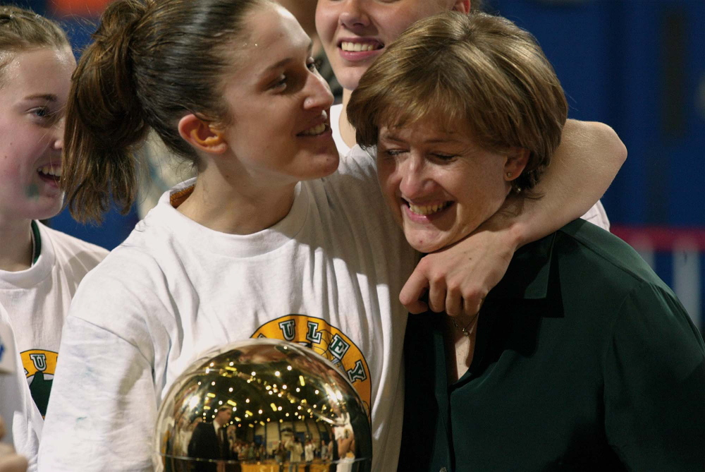 "Sarah Marshall and Coach Elizabeth Rickett join in the celebration after winning the state Class A girls' basketball championship in 2003. Marshall Ryan says her years at McAuley ""some of the best years of my life."""