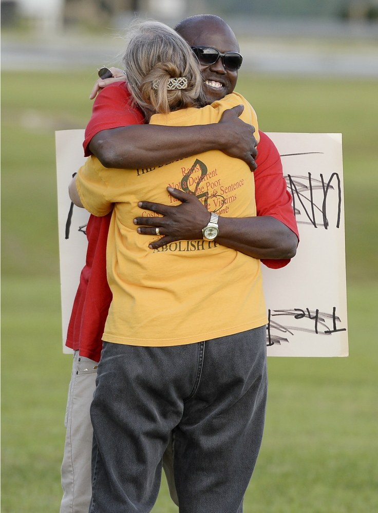 Herman Lindsey, who was exonerated from death row, back, greets a protester of the death penalty across the highway from the Florida State Prison last week.