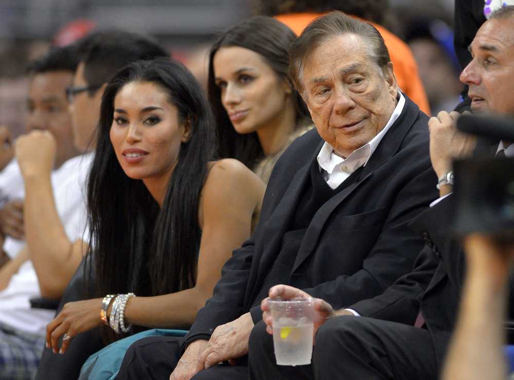 Los Angeles Clippers owner Donald Sterling, right, and V. Stiviano, left, watch the Clippers play the Sacramento Kings in Los Angeles on Oct. 25, 2013.