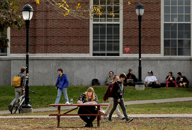 Charlotte Woodthorpe, a study abroad student from England, studies on the mall in front of the library at the University of Maine last fall.