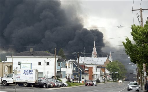 Smoke rises over Lac-Megantic from a deadly MM&A train derailment and explosion that killed 47 people in July 2013. A Canadian agency found that the railway had failed to report 20 previous derailments and two runaway train incidents in Canada.