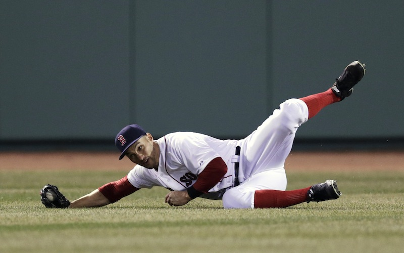 Boston Red Sox center fielder Grady Sizemore rolls as he makes the catch on a sacrifice fly by Texas Ranger Mitch Moreland, which scored Adrian Beltre, during the fourth inning of a MLB baseball game at Fenway Park, Monday, April 7, 2014, in Boston.
