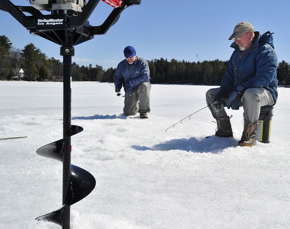 It's Opening Day for fishermen in the Naples area. but ice fishermen, like Roman Jozefiak of Scarborough, left, and Peter Brawn of Cape Elizabeth continue to ice fish on Sebago Lake Tuesday.