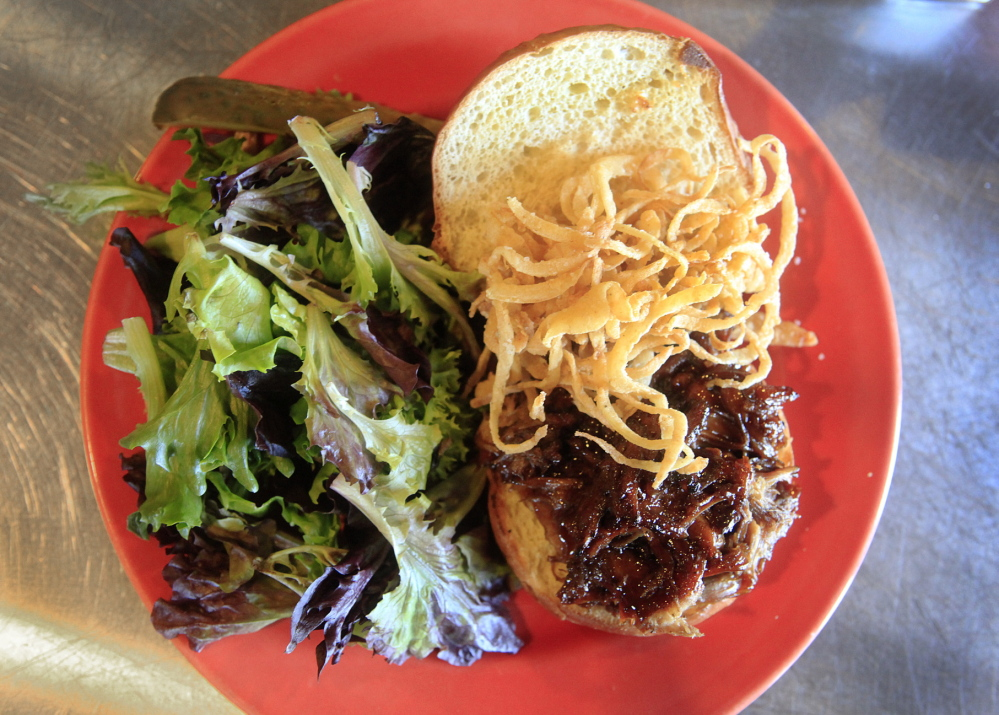 The Shipyard Brew Pub's pulled pork sandwich is served with onion strings, a side salad with house vinaigrette dressing and a pickle.
