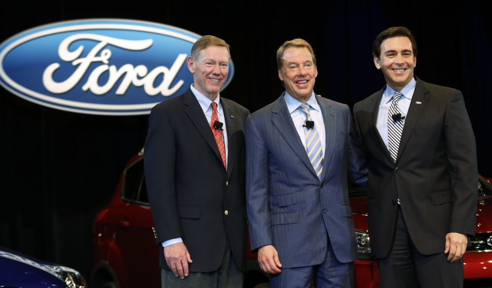 Ford Motor Co. President and CEO Alan Mulally, at left, stands with Executive Chairman Bill Ford Jr., middle, and Chief Operating Officer Mark Fields at a news conference in Dearborn, Mich., on Thursday. Mulally, who in 2006 was an industry newcomer from Boeing, helped lead the auto company through a massive and painful turnaround.