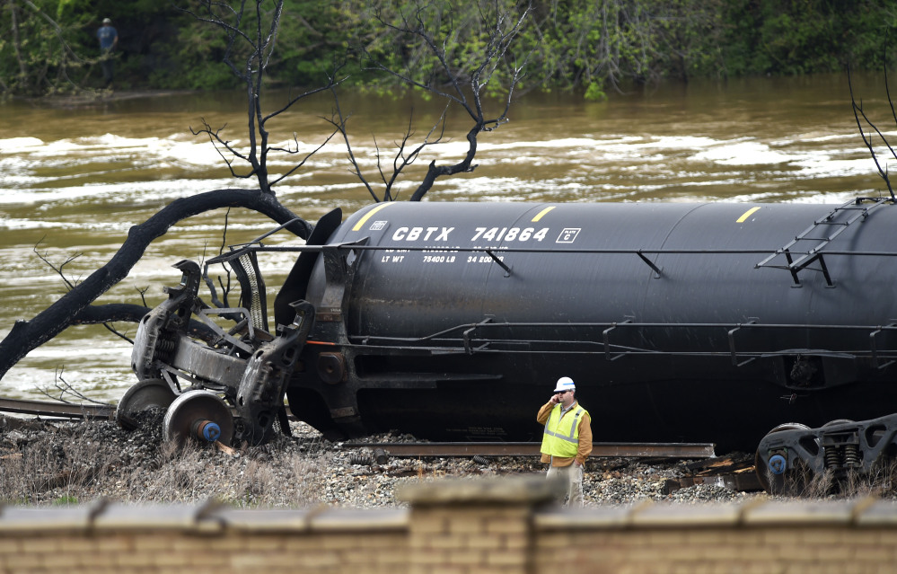 A worker stands on the bank of the James River near downtown Lynchburg, Va., on Thursday, beside a derailed and damaged tanker containing crude oil.