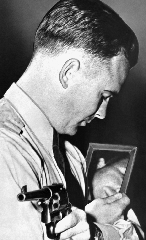 Federal Agent Walter R. Walsh demonstrates how to aim a gun using a mirror, in Quantico, Va., in 1937. He also trained Marine snipers and competed in the 1948 Olympics.