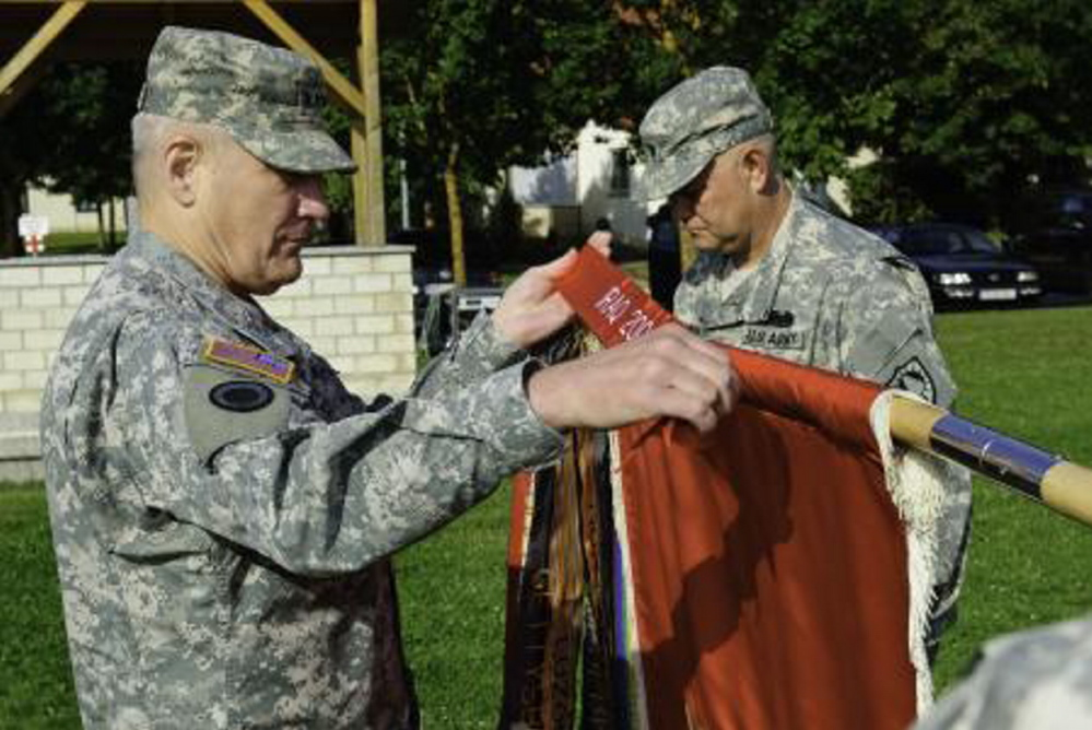 Gen. Carter Ham attaches a Meritorious Unit Commendation streamer to the colors of the Maine Army National Guard's 133rd Engineer Battalion at a 2009 ceremony in Hohenfels, Germany. The 133rd is Maine's oldest and largest military unit.