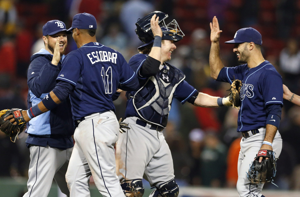 Tampa Bay Rays Yunel Escobar (11), Ryan Hanigan, second from right, and Sean Rodriguez, right, celebrate after defeating the Boston Red Sox 6-5 in the second game of a doubleheader in Boston on Thursday.