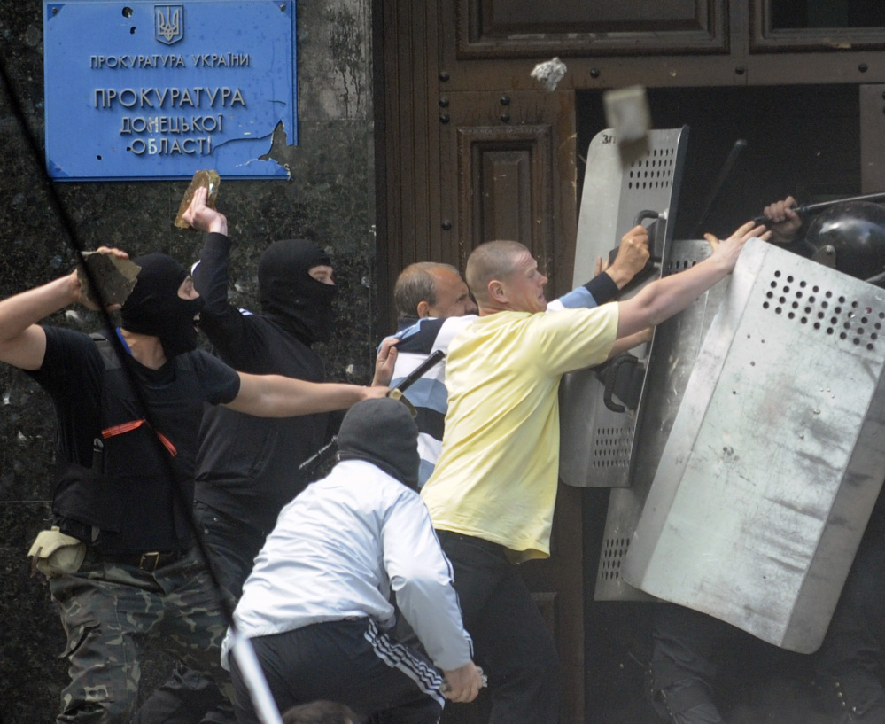 Pro-Russian activists try to wrestle shields from police in front of the regional administration building in Donetsk, Ukraine, on Thursday.
