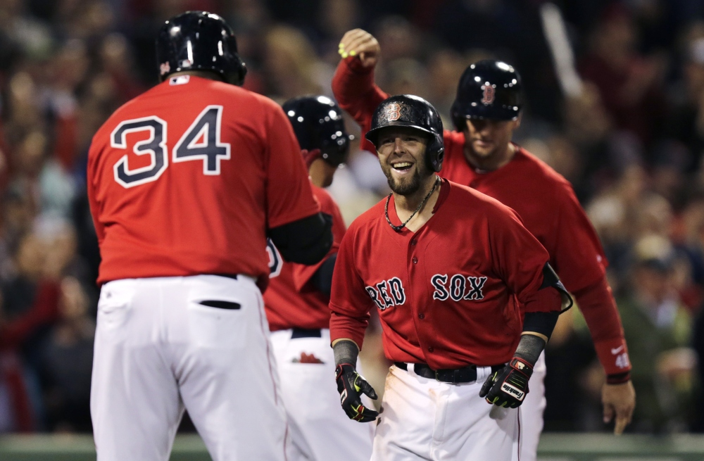 Red Sox second baseman Dustin Pedroia smiles as he is congratulated by teammate David Ortiz after his grand slam off Oakland Athletics pitcher Ryan Cook in the sixth inning at Fenway Park on Friday.