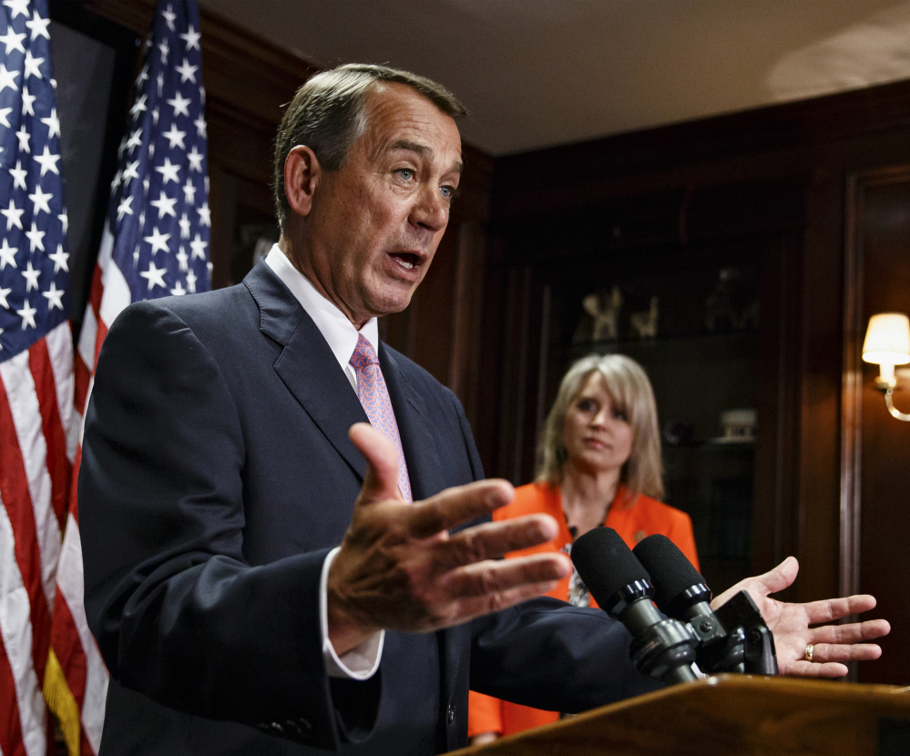 House Speaker John Boehner, joined by Rep. Renee Ellmers, R-N.C., talks to reporters after a Republican strategy meeting Tuesday in Washington.