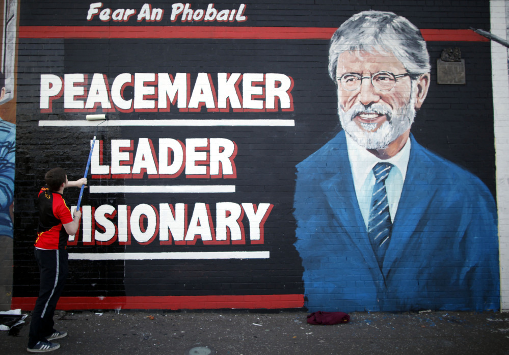 A man adds the finishing touch to a newly painted mural of Gerry Adams in West Belfast, Northern Ireland, on Friday, as police continued to question the Sinn Fein leader.