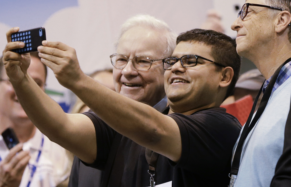 An unidentified shareholder takes a selfie with Warren Buffett, left, and Bill Gates, right, Saturday in Omaha, Neb.