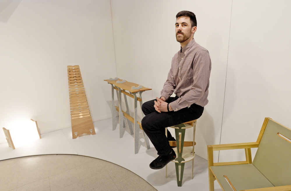 Rangeley Morton, a Maine College of Art grad who won a $15,000 Windgate Fellowship, poses with some of his work that is on display at MECA in Portland.