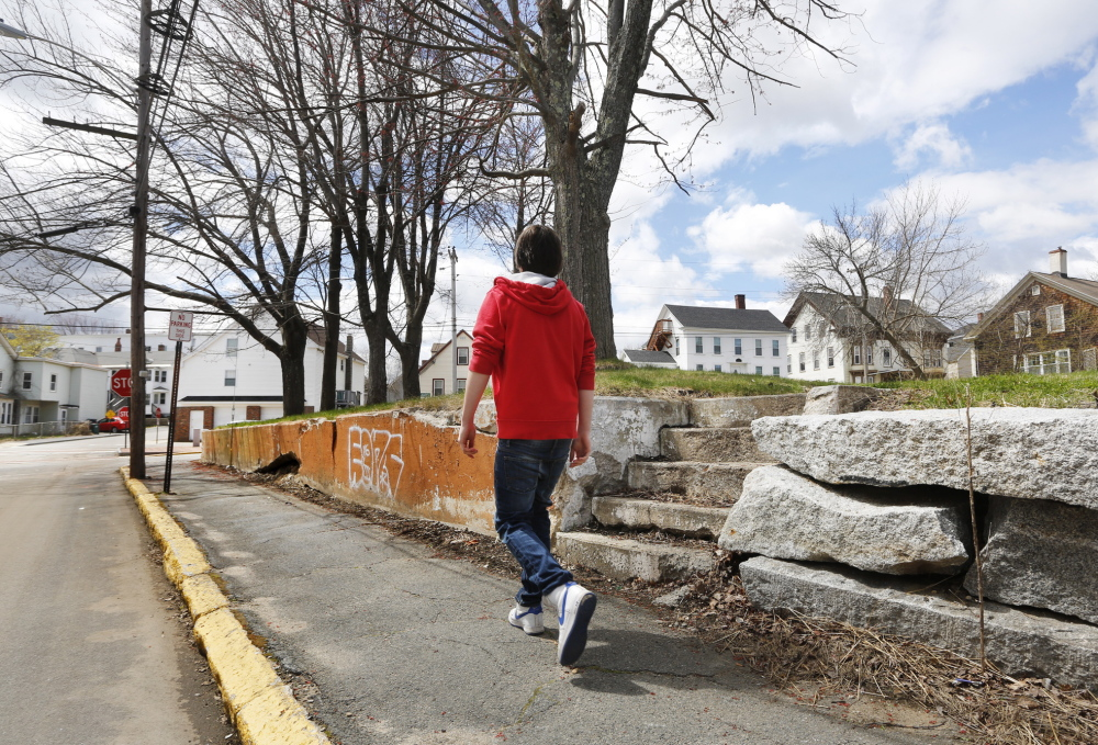 A boy passes vacant lots at the corner of Green and South streets in Biddeford. The city demolished the home of convicted murderer Rory Holland and another house to make way for a park expansion.