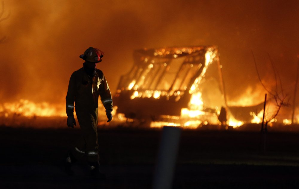 A firefighter walks past a burning mobile home at a mobile home park near Prairie Grove Rd. and Douglas during Oklahoma wildfires in south Logan County, Sunday, May 4, 2014. Firefighters worked through the night and into early Monday to battle a large wildfire that destroyed at least six homes and left at least one person dead after a controlled burn spread out of control in central Oklahoma.