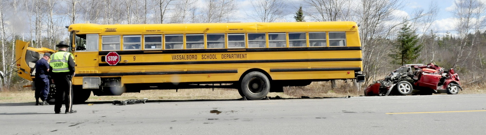 A small vehicle is pulled away from a Vassalboro School District bus after it slammed into the bus, which was parked on Route 3 in South China on Monday.