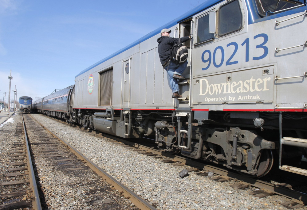 An engineer with Amtrak climbs toward the cab of a Downeaster train in Portland in 2009. About 65 people use the train to commute to their jobs in Boston from Portland and from Maine train stations south of Portland.