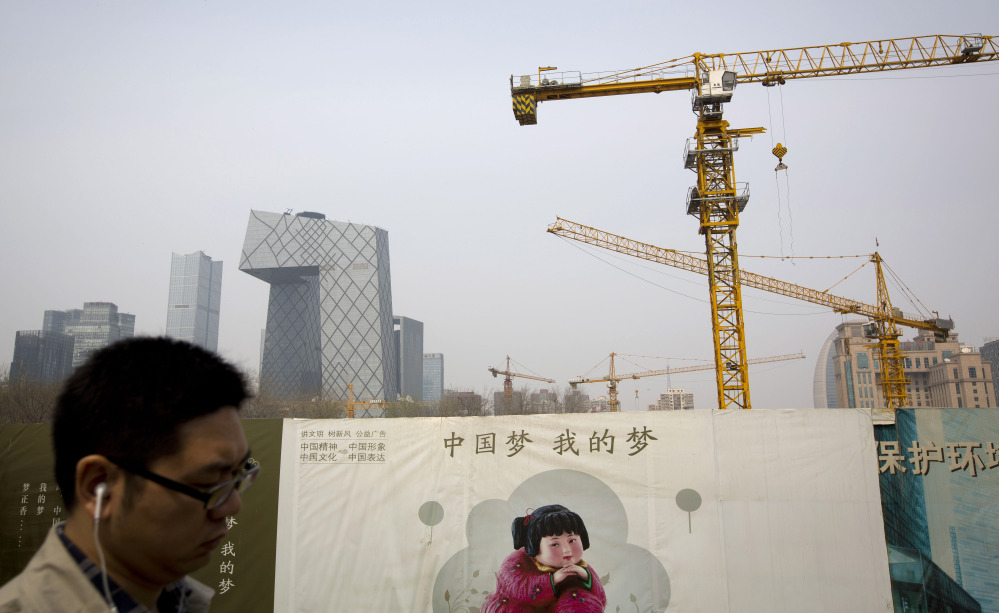 "A man walks past a Chinese government propaganda billboard with the words ""China Dream, Is My Dream"" near a construction site in Beijing. China's January-to-March growth slowed to 7.4 percent, its weakest quarter since the 2008-2009 global crisis, but that would still qualify as explosive for most of the world's economies."