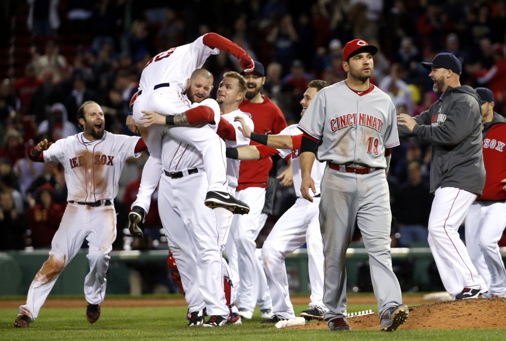 Boston Red Sox center fielder Grady Sizemore (38) jumps into the arms of teammate Jonny Gomes as he and teammates celebrate his walk-off single to defeat the Cincinnati Reds 4-3 in the 12th inning of a baseball game at Fenway Park in Boston, Tuesday, May 6, 2014. Reds first baseman Joey Votto (19) walks off the field.