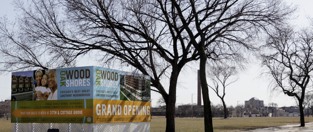 A corner billboard sits in a vacant lot, advertising where a variety of housing will be built in Chicago.