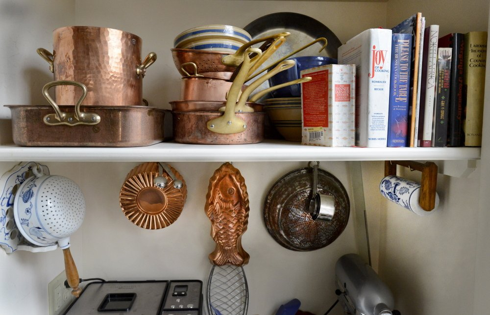 Kitchen implements and cookbooks line the shelves.