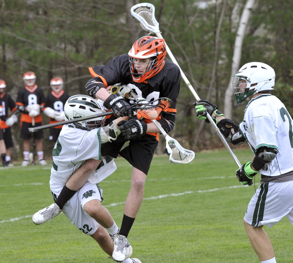 Brad McLellan of North Yarmouth Academy is checked by Cooper Chap of Waynflete as Reilly Musgrave moves in Tuesday during Waynflete's 6-4 victory in a boys' lacrosse game at Fore River Fields in Portland.