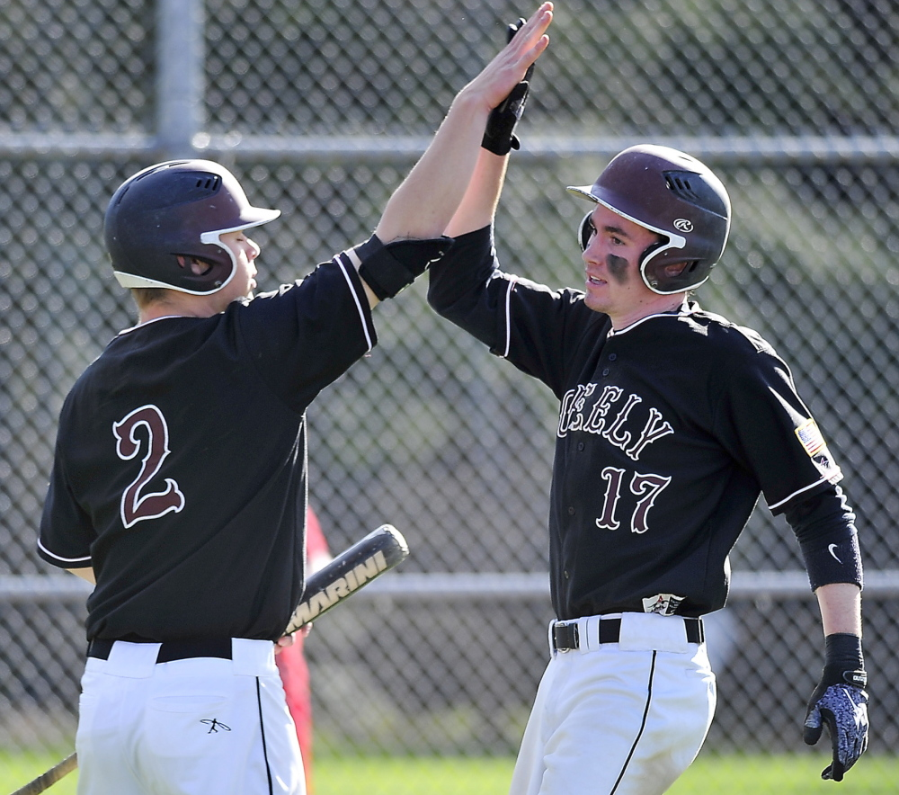Will Bryant of Greely, left, welcomes Sam Porter, who scored an early run Wednesday against Yarmouth. Greely improved its record to 5-1 by scoring in the bottom of the seventh inning for a 5-4 victory.