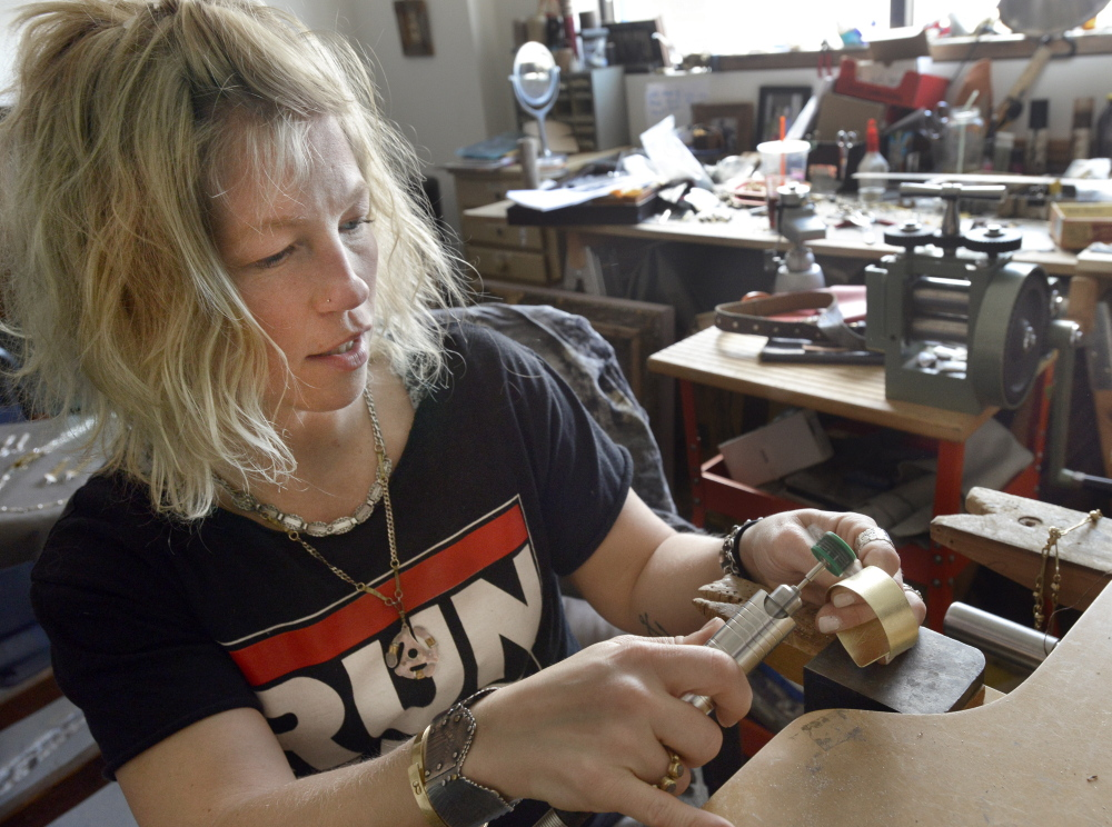 "Hannah Tarkinson, seen polishing a bracelet at her Portland studio, is an avowed supporter of Creative Portland's efforts. ""I love that Portland is trying to bring people together and connect them,"" she said."