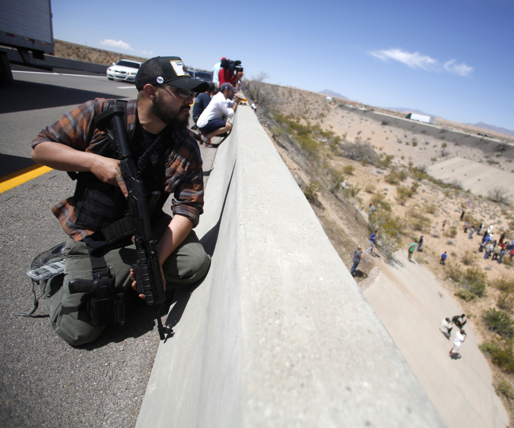 Locked and loaded, Eric Parker of Idaho keeps watch from a bridge along with other supporters of controversial Nevada cattleman Cliven Bundy last month.