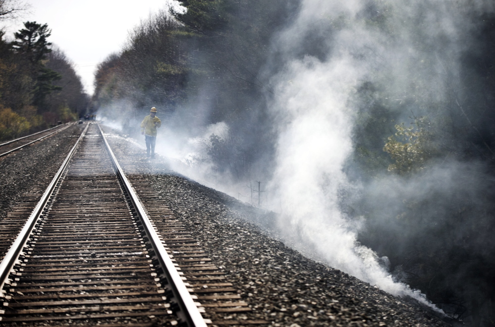 """A firefighter walks near railroad tracks where a brush fire started Thursday and spread to the Wagon Wheel RV Resort and Campground. Some residents fought the fires themselves, including Bob Kelly and Lori Gramlich. """"It was scary,"""" Gramlich said. """"The wind shifted and the fire came back toward us. I had to get out of there. I was having a hard time breathing."""""""