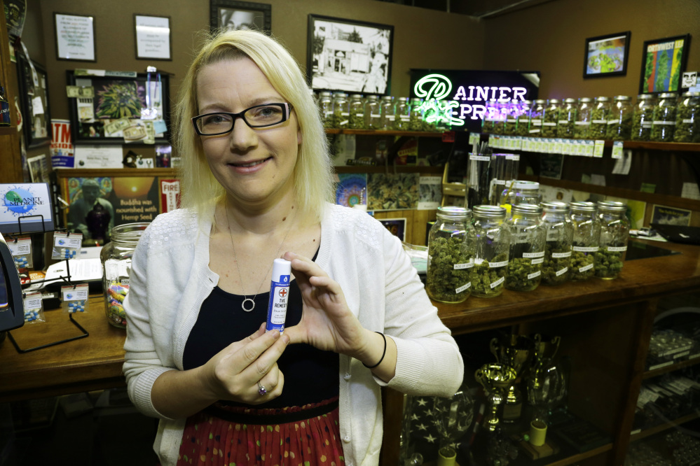 Kari Boiter of Tacoma, Wash., poses for a photo at Rainier Xpress, a medical marijuana dispensary in Olympia, Wash. More than 20 states allow the medical use of marijuana, but major insurers still don't cover the pricey treatment for patients seeking relief.