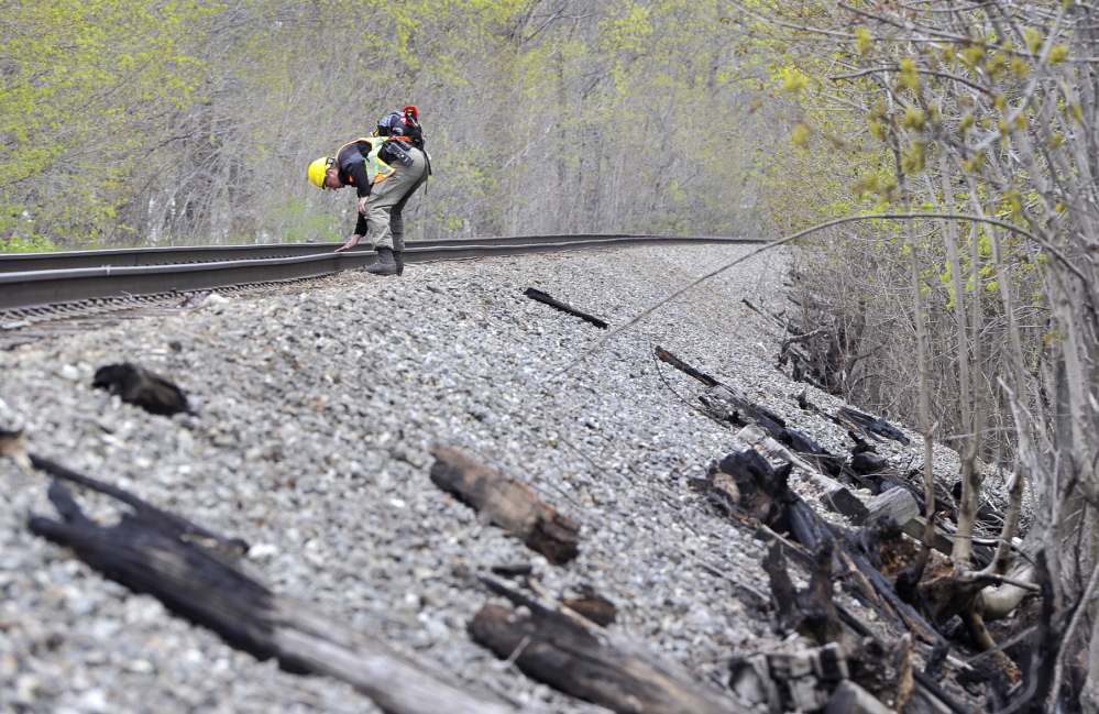 Maine Forest Ranger Matthew Bennett looks for evidence Friday that a train caused a fire along train tracks in Saco on Thursday. Some witnesses report seeing sparks shooting from a freight train, while others say they saw a swirl of burning leaves and debris in the air.