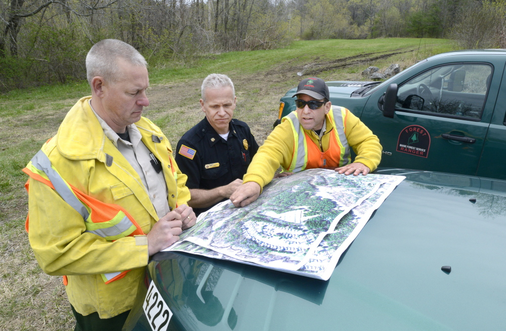 Old Orchard Beach, ME - MAY 9: Maine Forest Rangers Mark Rousseau (left) and John Leavitt (right) are joined by Saco Fire Dept. deputy chief Robert Martin in going over a map as they assess fire damage along the train tracks in Saco. (Photo by John Patriquin/Staff Photographer)