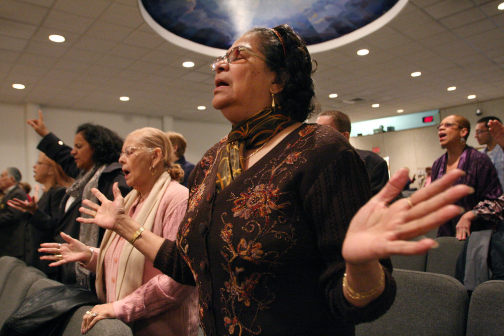 Maria Antonetty, foreground, attends a service at the Primitive Christian Church in New York in April 2009. Latinos in the United States are abandoning Roman Catholicism in increasing numbers to become evangelical Protestants or to leave organized religion.
